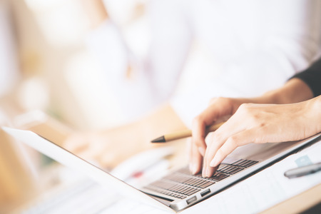 Side view of girls hands using laptop computer placed on messy office desktop Stock Photo