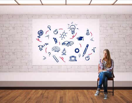 thoughtful: Thoughtful young woman sitting on chair in modern interior with scientific sketches on whiteboard. Education concept Stock Photo