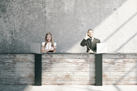 Attractive young businessman and woman at wooden reception desk in interior. 3D Rendering Standard-Bild