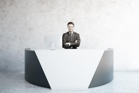 recepcion: Atractivo joven hombre de negocios en el escritorio de recepción limpia en el interior. Representación 3D Foto de archivo