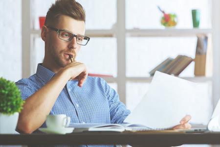 Portret van aantrekkelijke Kaukasische kerel met document in hand op het werk