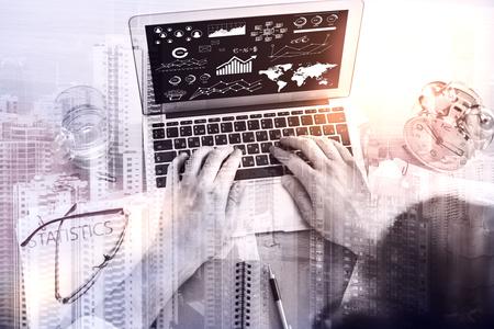 exposicion: Hombre de negocios usando la computadora portátil con gráficos digitales en la pantalla. Exposicion doble. Fondo de la ciudad. Concepto de negocio Foto de archivo