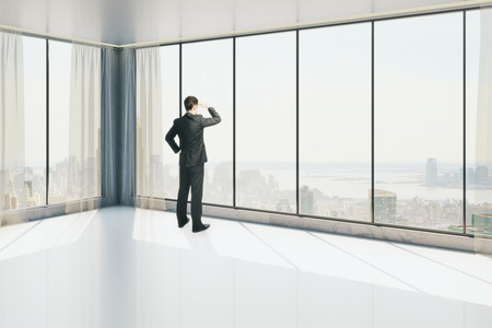man looking out: Side view of businessman in modern interior with city view, looking into the distance. Research concept. 3D Rendering Stock Photo