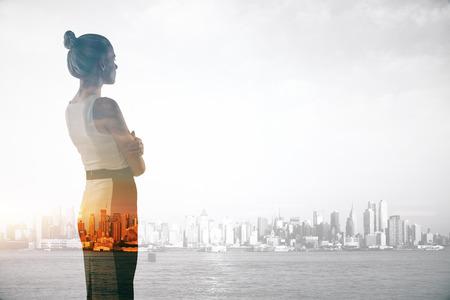 Aantrekkelijke jonge zakenvrouw op abstracte stad achtergrond met kopie ruimte. Dubbele belichting. onderzoek concept