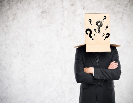 masquerader: Businessman with folded arms and cardboard box with question marks covering head on concrete background. Confusion concept
