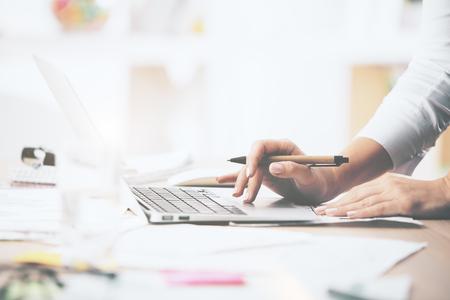 乱雑なオフィスのデスクトップ上に配置するノートブックを使用して女性の手のクローズ アップ 写真素材