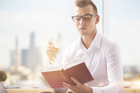 Portrait of handsome caucasian gentleman reading book at workplace. Education concept