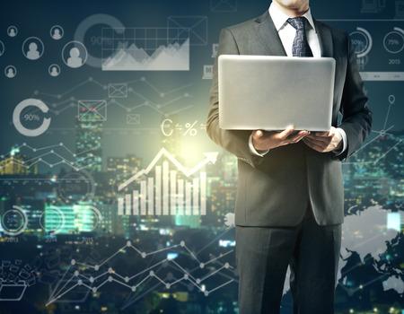 ビジネス グラフで抽象街背景にノート パソコンを使用しての実業家