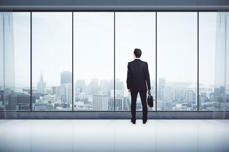 Achter mening van zakenman met aktentas in modern interieur met uitzicht op de stad, op zoek in de verte. Onderzoek concept. 3D Rendering