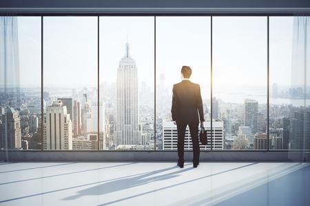 Vista posteriore di uomo con la valigetta in interni moderni con vista sulla città, guardando in lontananza. concetto di ricerca. Rendering 3D