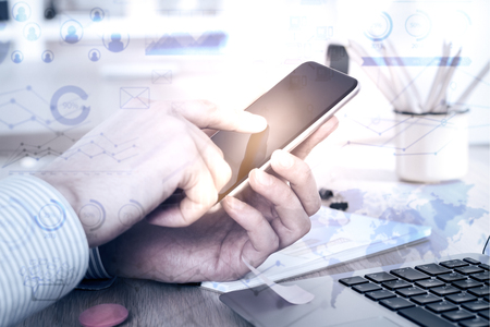 business finance: Close up of male hands using smartphone with abstract digital charts at workplace