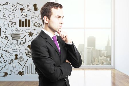 thoughtful: Thoughtful businessman in room with business chart. Success concept Stock Photo