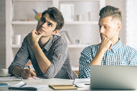 person writing: Two handsome white boys working on project in modern office