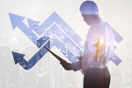 double flèche: Side view of businessman with document in hands standing on abstract city and business chart background. Double exposure Banque d'images