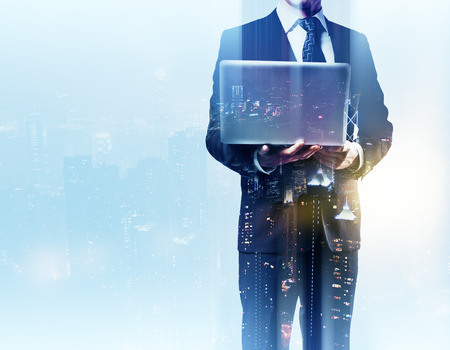 executive search: Businessman with laptop standing against a city panorama. Mock up. Double exposure