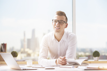 european: Portrait of attractive caucasian businessman working on project at modern workplace Stock Photo