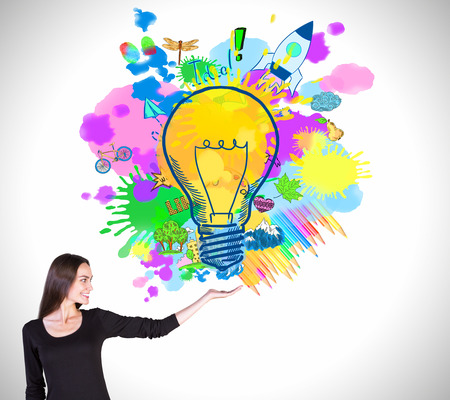 Happy european female holding colorful light bulb drawing on light background. Creative idea concept