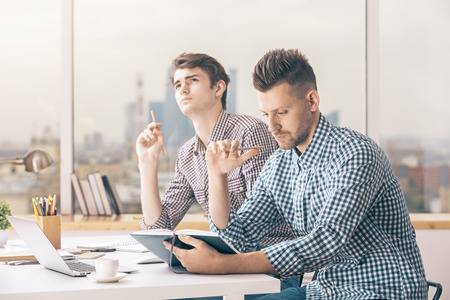 Two handsome caucasian guys working on project in modern office