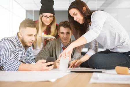 teamwork concept: Attractive young team watching something on smartphone at workplace. Teamwork concept Stock Photo