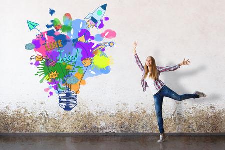 Feliz niña europea en sala de hormigón grungy con lámpara creativa y boceto de nave espacial. Idea de inicio exitosa