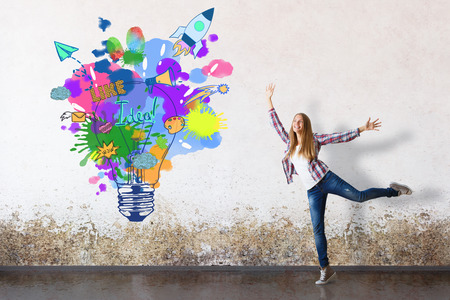 Gelukkig Europees meisje in grungy concrete ruimte met creatieve lamp en ruimteschip schets. Succesvolle startup idee Stockfoto
