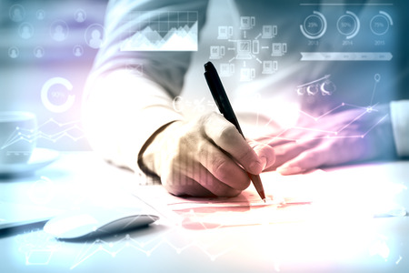 charts: Close up of man doing paperwork at workplace with creative business charts and diagrams. Toned image. Accounting concept