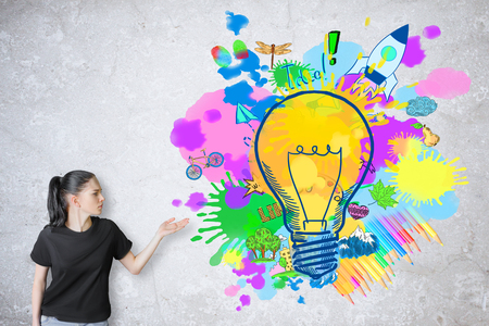 concept and ideas: Pretty white girl showing colorful lightbulb sketch on concrete background. Creative ideas concept