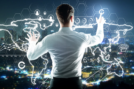 information analysis: Back view of businessman pointing at abstract digital charts and maps on bright night city background. International business concept