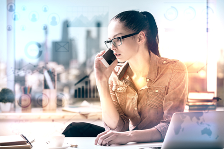 interaction: Attractive caucasian woman at workpace with abstract business charts talking on the phone and working on project. Finance concept. Toned image