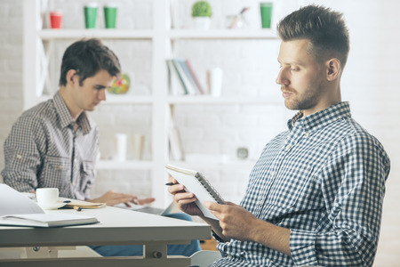 hombre escribiendo: Retrato del hombre caucásico guapo en escritura moderna de la oficina en la libreta espiral. Blurry colega en el fondo. Joven, escritor, concepto
