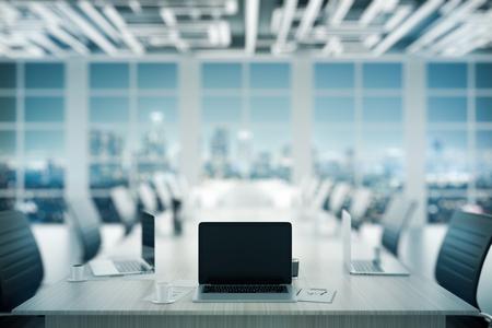 Gros plan d'un ordinateur portable vierge placé sur une table de conférence en bois dans un intérieur sombre. Mock up, rendu 3D. Concept de réunion