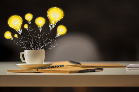 Creative image of office desktop with abstract drawn lamp balloons in coffee cup. Idea concept Stock Photo