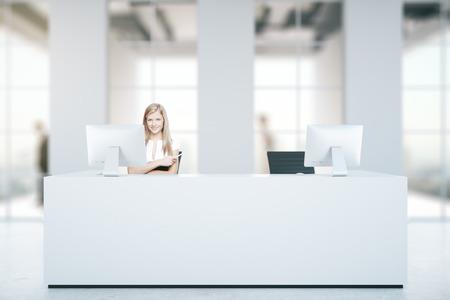 Aantrekkelijke blanke vrouw bij witte receptie met computers in onscherpe beton interieur met daglicht. Business concept. 3D Rendering