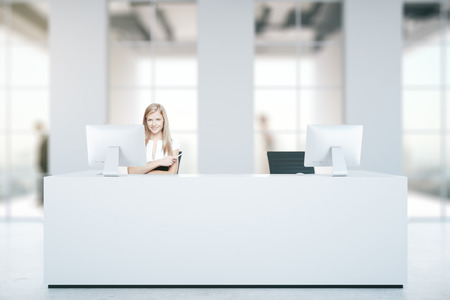 reception counter: Attractive caucasian woman at white reception desk with computers in blurry concrete interior with daylight. Business concept. 3D Rendering