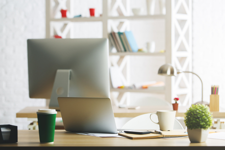 design office: Creative designerworkplace with laptop, lamp, coffee cup, plant and other items. Modern office concept