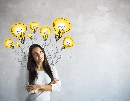 Mooie Europese vrouw denken op concrete achtergrond met abstracte getrokken lampen. idee concept Stockfoto
