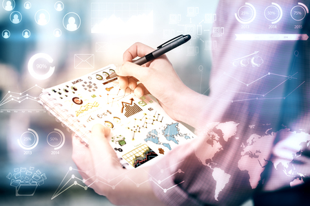 Close up of female hands drawing colorful business graphs and diagrams in spiral notepad on blurry background with digital charts. Accounting concept