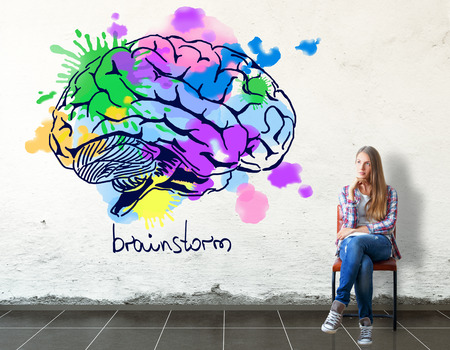 smart woman: Thoughful european girl sitting on chair in concrete room with bright human brain sketch on wall. Creative thinking concept. 3D Rendering