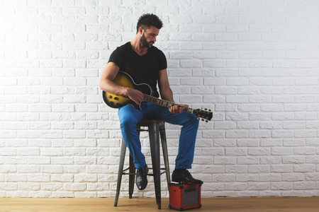 Attracive caucasian man in casual clothing playing the guitar while sitting in interior with white brick wall and wooden floor. Musician concept