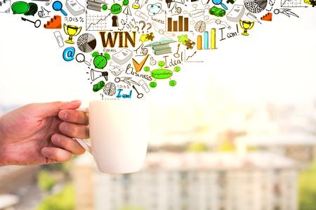 De koffiemok van de handholding met creatieve bedrijfstekeningen op de onscherpe achtergrond van de de zomerstad. Succes concept