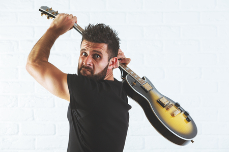 Furious european man about to smash his electric guitar on white brick background. Anger concept