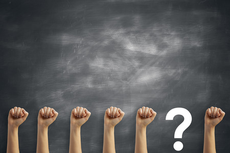 multiple: Row of female fists and question mark on chalkboard background. Determination and confusion concept Stock Photo