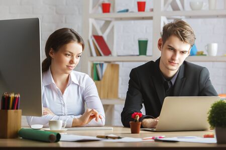 bloggers: Portrait of attractive european man and woman in modern office working together. Team work concept Stock Photo