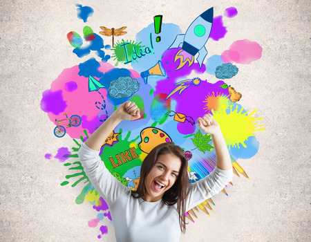 Cheerful caucasian woman on concrete background with colorful sketch. Creativity concept