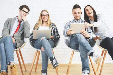 Group of attractive caucasian guys and girls sitting on modern chairs and using laptops. Technology, teamwork and communication