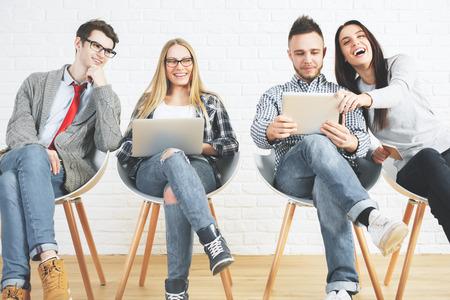 Gruppo di attraenti ragazzi e ragazze caucasici seduti su sedie moderne e utilizzando computer portatili. Tecnologia, lavoro di squadra e comunicazione Archivio Fotografico - 72564189