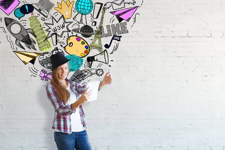 business woman: Cheerful caucasian girl with hat holding notepad on concrete background with cool doodles. Inspiration and social media concept Stock Photo