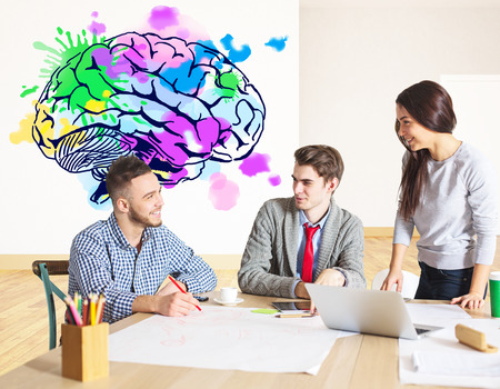 Attractive young businesspeople working on project together in modern office with colorful brain sketch. Creative thinking concept