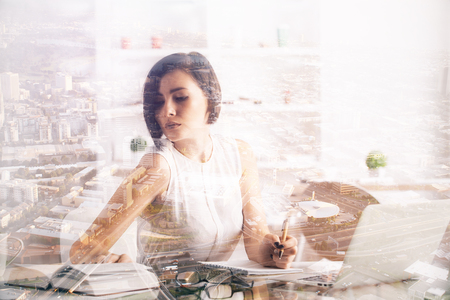 office life: Attractive caucasian lady at workplace on abstract city background. Office life concept. Double exposure Stock Photo