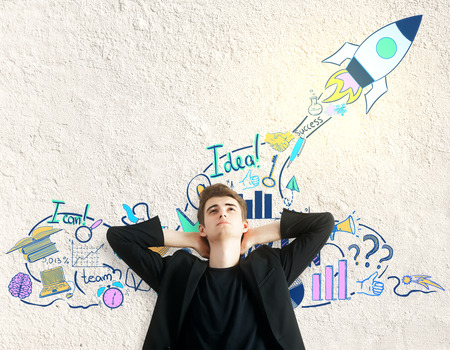 young business man: Relaxing young man on textured concrete background with business sketch. Entrepreneurship concept